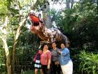 Mi familia tica posing in front of the T-Rex at Zoo Ave